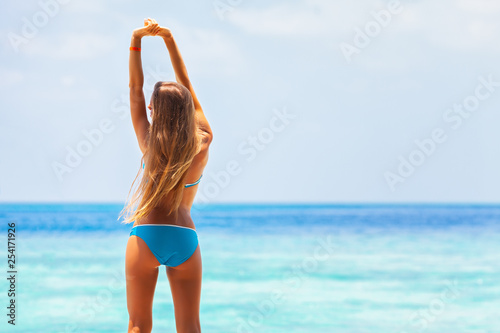 Fototapeta summer exotic tropical vacation wallpaper - beautiful young sexy blonde girl with perfect sport body relaxing on the white sand caribbean maldives beach and making gymnastics exercise with sunbath obraz na płótnie