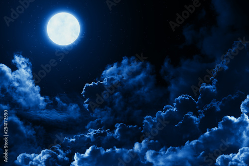 Obraz Mystical bright full moon in the midnight sky with stars surrounded by dramatic clouds. Dark natural background with twilight night sky with moon and clouds - fototapety do salonu