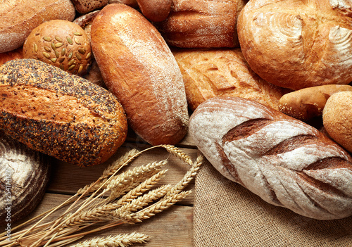 Poster Brood assortment of baked bread on wooden background