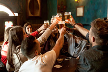 Group Of People Celebrating In A Pub Drinking Beer
