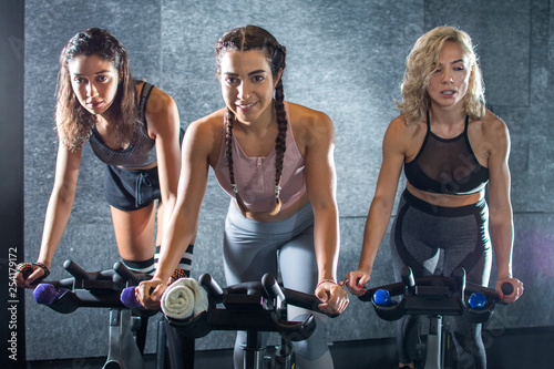 Group of attractive women pedaling on stationary bikes at gym.