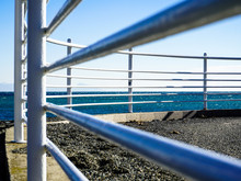 White Railing In Front Of A Blue Sea