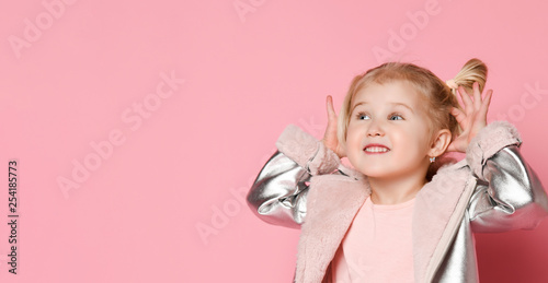 Fotografia, Obraz  Portrait of a little girl looking to the side of the frame and showing teasers o