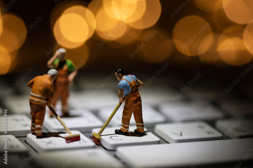 Fototapeta Miniature people cleaning white keyboard computer.