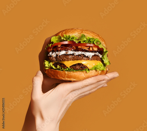 Fototapeta Woman hands hold big double cheeseburger burger sandwich with beef and bacon on yellow obraz