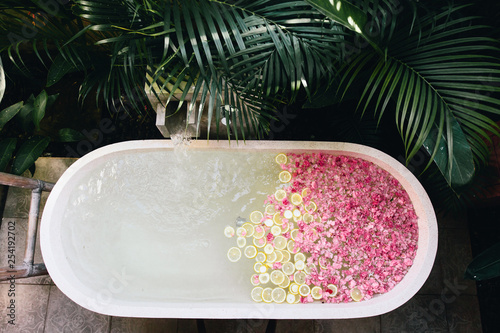 Canvas Print Bath tub filling with water with flowers and lemon slices