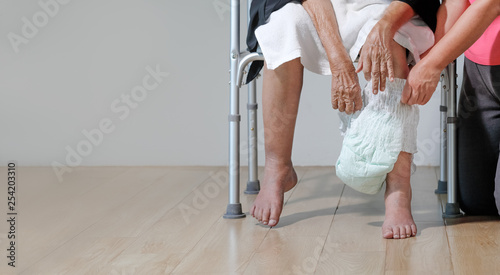 Fotografía  elderly woman changing diaper with caregiver