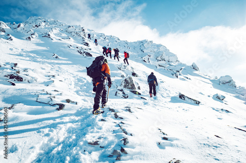 Canvas Print A group of climbers ascending a mountain in winter