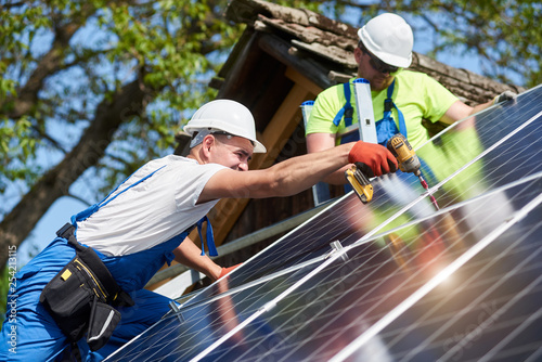 Fotografie, Tablou  Two workers technicians installing heavy solar photo voltaic panels to high steel platform