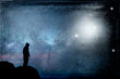 canvas print picture - A lone hooded figure silhouetted, standing on a hill looking at a galaxy at night with UFOs floating in the sky. With a grunge, vintage edit.