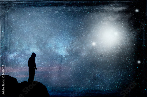 Photo sur Aluminium UFO A lone hooded figure silhouetted, standing on a hill looking at a galaxy at night with UFOs floating in the sky. With a grunge, vintage edit.