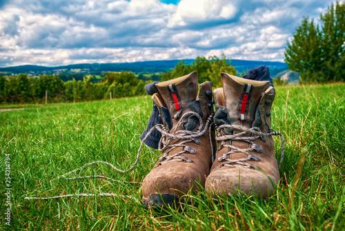 Wandern in Deutschland: Gebrauchte Wanderschuhe im Gras Fototapeta
