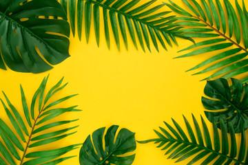 Skład lato z miejsca na kopię. Rama wykonana z zielonej tropikalnej palmy i liści Monstera na pastelowym żółtym tle. Koncepcja lato. Płaski układ, widok z góry