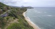 Aerial: Overcast day over beach and ocean panning down
