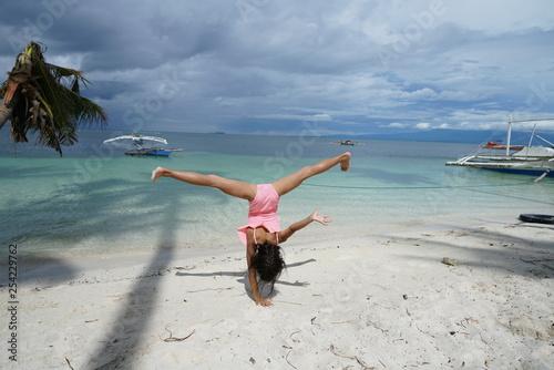 Fotografie, Obraz  Young girl doing cartwheel along beach on Siquijor Island, Philippines