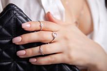 Closeup Beautiful Brunette Girl With Long Hair In Silver Jewelry Earrings, Rings, Bracelet And Necklace In Decollete. Сoncept Gentle, Elegant, Delicate, Romantic Jewelry, Bijouterie On Model