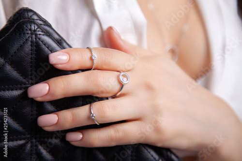Foto  Closeup beautiful brunette girl with long hair in silver jewelry earrings, rings, bracelet and necklace in decollete