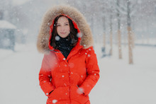 Lovely Female Model In Red Jacket, Stads Outdoor During Snowfall, Looks With Dark Eyes At Camera, Going To Have Stroll With Boyfriend, Breathes Fresh Air. People, Winter Time And Free Time Concept
