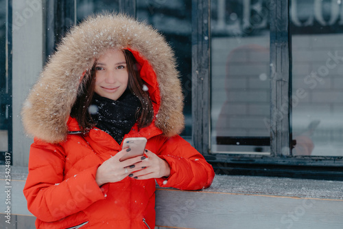 Pleasant looking young female in red jacket, holds modern smart
