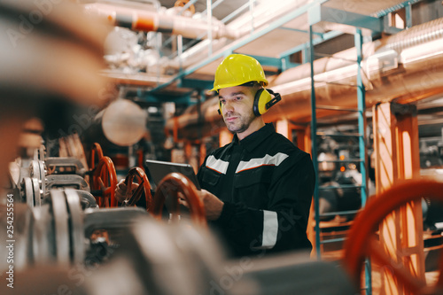 Young Caucasian hardworking heavy industry worker in protective suit and helmet using tablet and screwing valve.