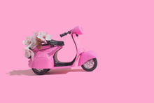 Pink Retro Toy Bike Delivering Bouquet Of Flowers Box On Pink Background. February 14 Card, Valentine's Day. Flower Delivery. 8 March, International Happy Women's Day. Mother's Day