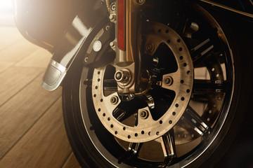 widelec przedni motocykla z przednim kołem, tarczą hamulcową, cylindrem hamulcowym. Ścieśniać. Nieostrość