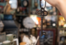 Woman's Hand Holding An Antique Key On Blurred Background
