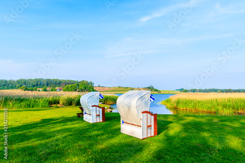 Foto auf Leinwand Grun Wicker beach chairs on green area along lake shore in Seedorf village, Baltic Sea, Germany