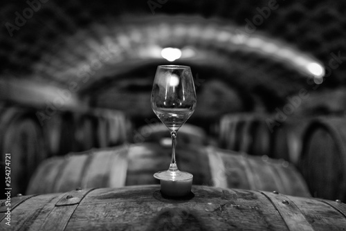 Fotografía Glass standing on barrel in wine cellar. Black & white photo.