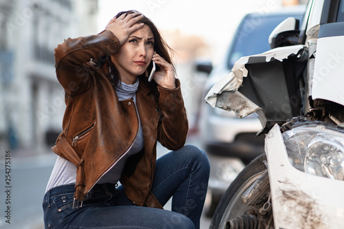 Young woman crying while calling for help after car accident.