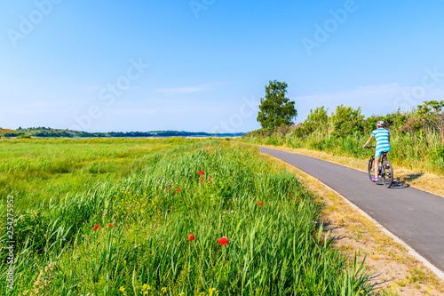 Montage in der Fensternische Nordeuropa Young woman cyclist riding bicycle on route from Baabe to Moritzdorf village in countryside spring landscape, Ruegen island, Baltic Sea, Germany