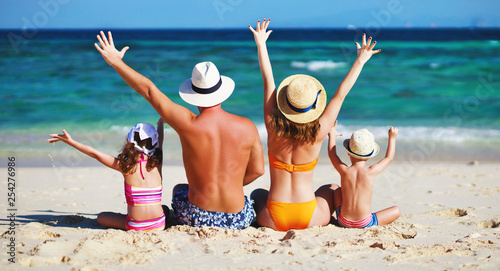Fototapeta happy family father, mother and children backs on  beach at sea. obraz