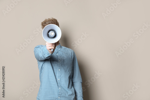 Photo Young man with megaphone on color background. Space for text