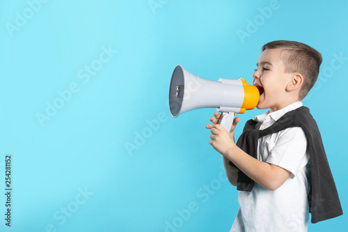 Fotografía  Cute funny boy with megaphone on color background. Space for text