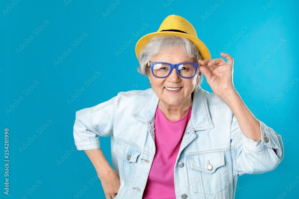 Fototapeta Portrait of mature woman in hipster outfit on color background