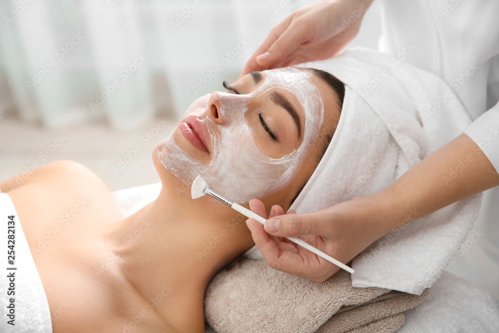 Fototapeta Cosmetologist applying mask on client's face in spa salon