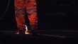 Slow motion view of a road worker using a Thermal lance to burn white lines from a main road before repainting at night.