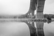 concrete bridge with fog in black and white crossing the river
