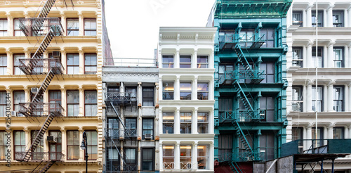Photo Stands New York Exterior view of a block of colorful old historic buildings along Greene Street in the SoHo neighborhood in New York City with pattern of windows and fire escapes