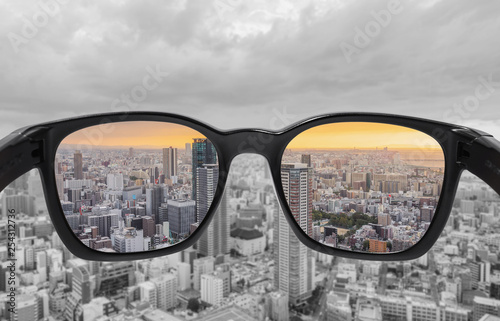 Looking through glasses to city view in sunset Wallpaper Mural