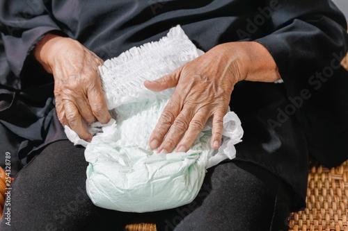 Canvastavla  elderly woman changing diaper