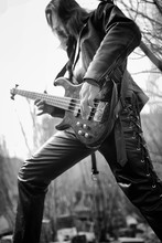 Rock Guitarist Outdoor. A Musician With A Bass Guitar In A Leather Suit. Metalist With A Guitar On The Background Of Industrial Steps.