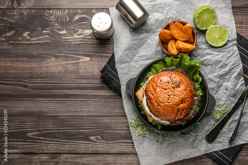 Composition with tasty burger on table Tableau sur Toile