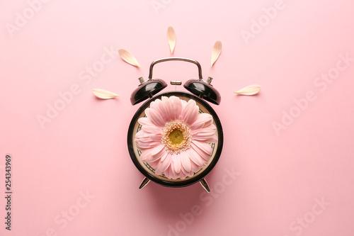 Obraz Alarm clock with flower on color background - fototapety do salonu