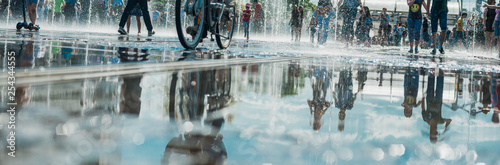 plakat Reflection of the crowd of merry people in the city fountain, in the pool. Bright sunny spring or summer day.