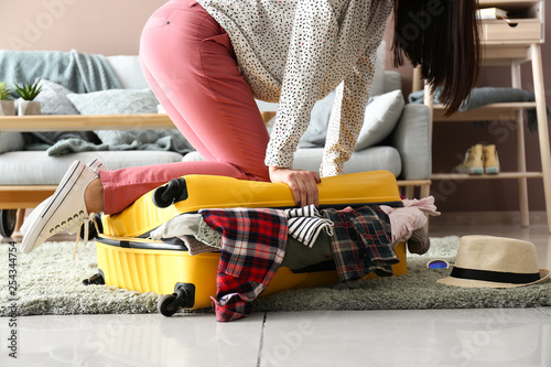 Woman trying to close suitcase with a lot of things Fototapete