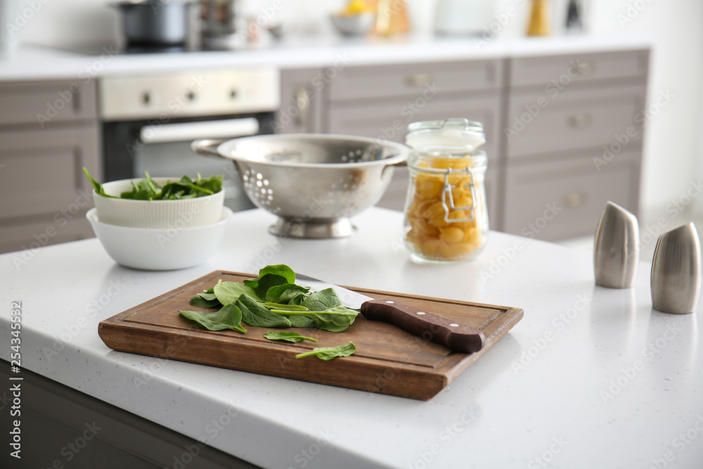 Fototapety, obrazy: Fresh herbs with cutting board on table in kitchen