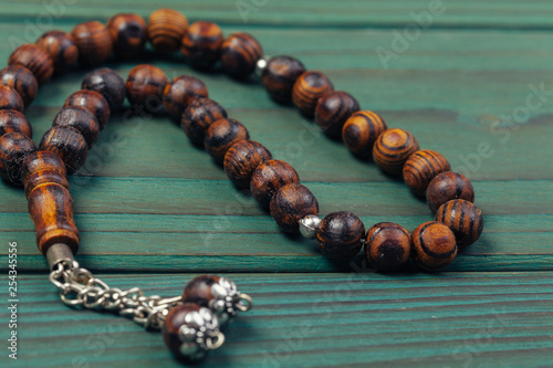 Muslim prayer beads on wooden background close up