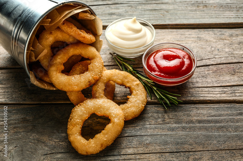 Fototapeta Overturned bucket with tasty onion rings and sauces on wooden table obraz