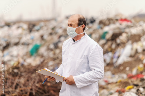 Valokuva  Ecologist in white uniform and mask on face holding clipboard and evaluating damage